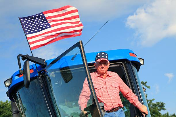 Agriculture: Patriotic American Farmer on Tractor with Flag stock photo