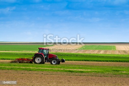 Farm tractor plowing  the land