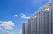 agriculture tank against blue sky background, seed steel silos, grain metal storage container.