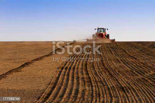 istock Agriculture tractor sowing seeds and cultivating field 177293744