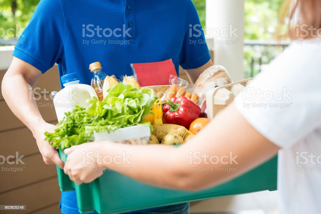 Agrocery delivery man delievering food to a woman at home A grocery store delivery man wearing a blue polo-shirt delivering food to a woman at home Accessibility Stock Photo