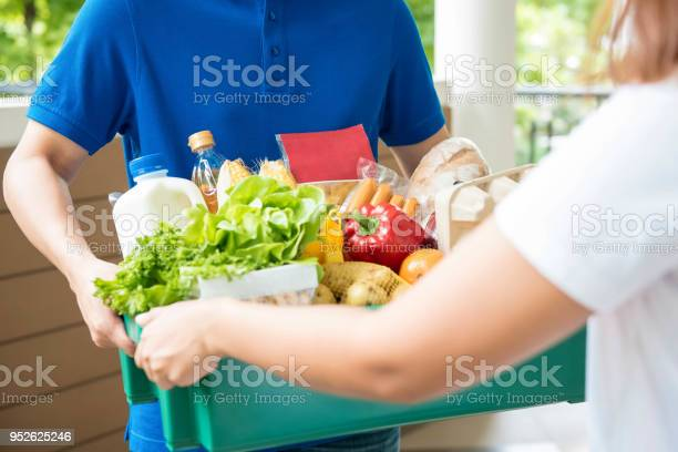 Agrocery Delivery Man Delievering Food To A Woman At Home Stock Photo - Download Image Now