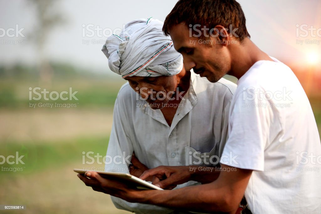 Agronomist consulting with farmer outdoor in the field stock photo