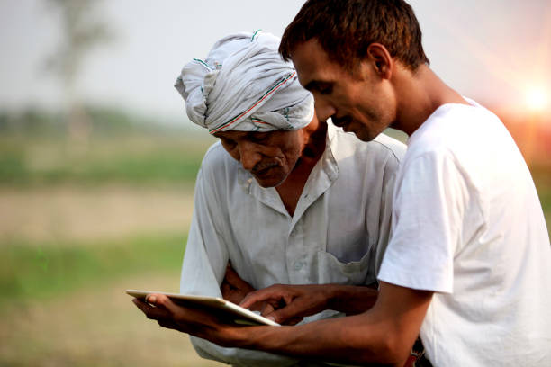 Agronomist consulting with farmer outdoor in the field Young agronomist Standing during sunset near green field with senior Farmer holding ipad & showing something in the Ipad to the farmer. developing countries stock pictures, royalty-free photos & images