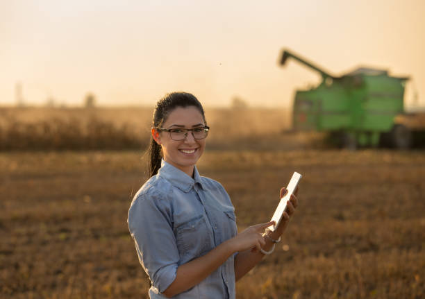 Agronomist with tablet in front of combine harvester Pretty young woman with tablet standing in soybean field with combine harvester working in background biodiesel stock pictures, royalty-free photos & images