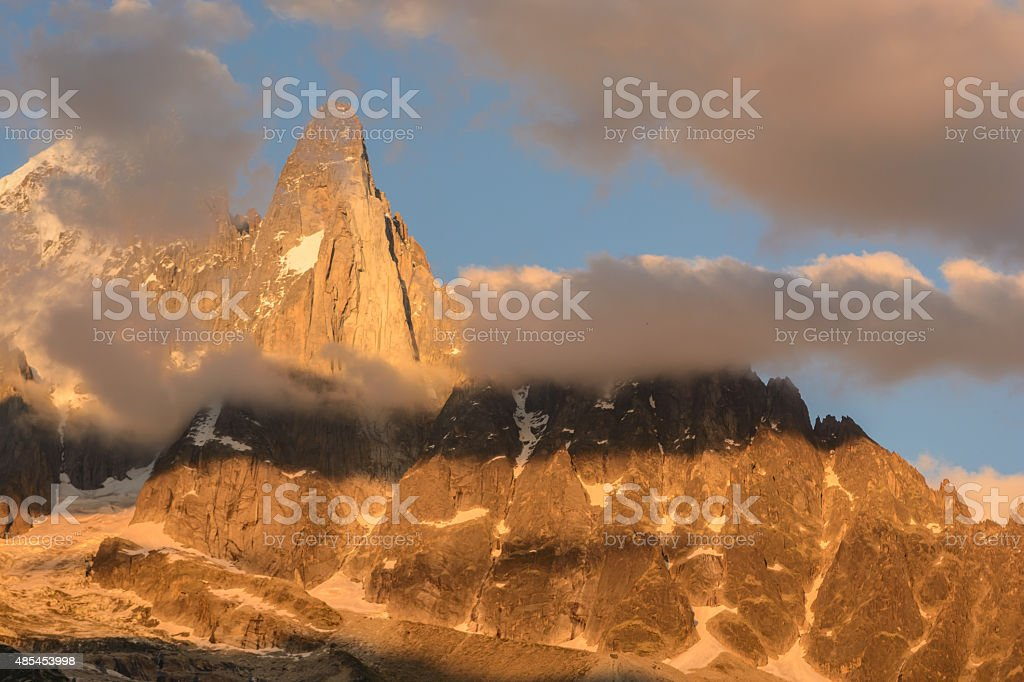 Aguille du Dru north face  clouds lifting at sunset alpenglow stock photo