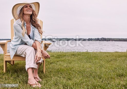 Shot of a beautiful young woman relaxing on a chair next a lake