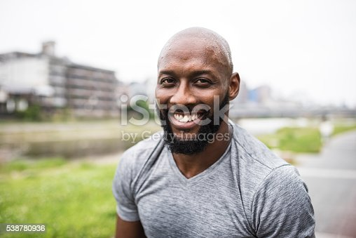An African American adult man working out in nature and smiling