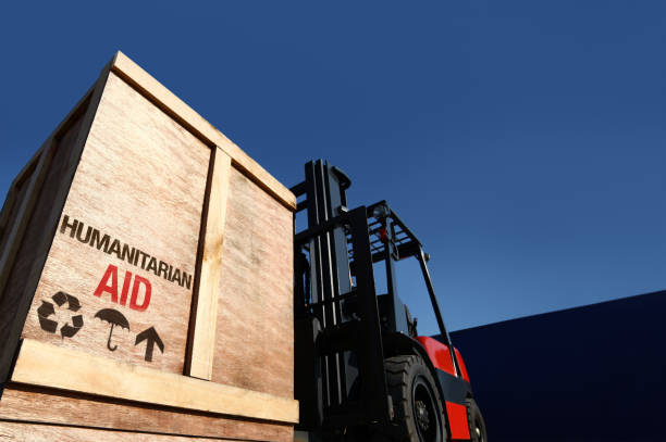 Aid cargo on forklift truck. Forklift truck with boxes on pallet. Aid cargo concept. social responsibility stock pictures, royalty-free photos & images
