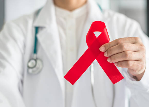 Aids red ribbon in doctor's hand for World aids day and HIV virus awareness concept Aids red ribbon in doctor's hand for World aids day and HIV virus awareness concept hiv stock pictures, royalty-free photos & images