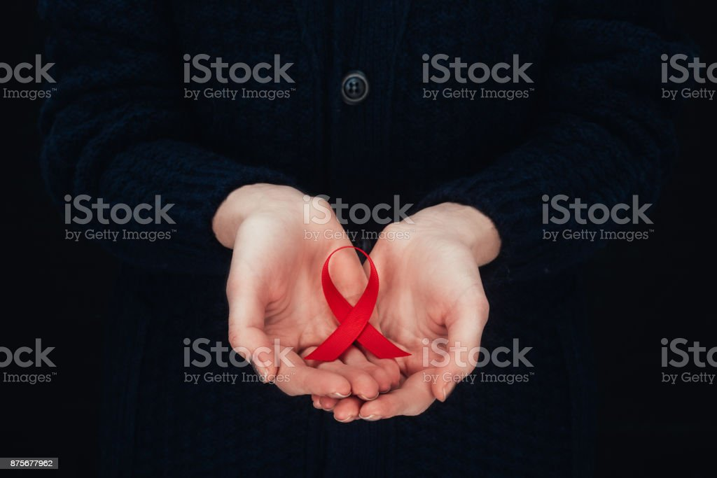 aids ribbon in hands stock photo
