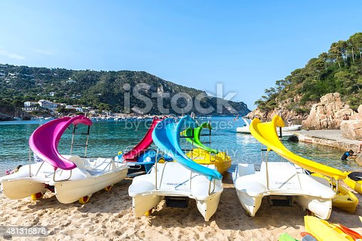 Girona, Spain - June 30, 2015: Kayaks, canoes and pedalos with slides on the beach Aiguablava in Costa Brava, Catalonia, Spain
