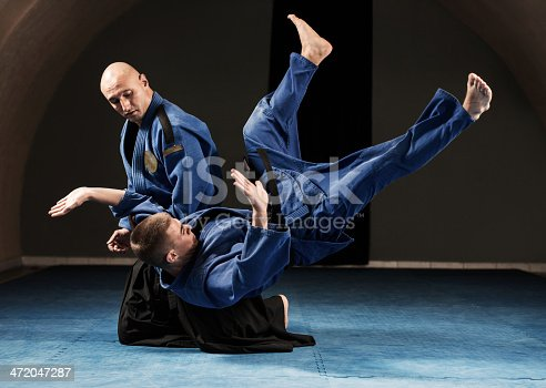 Aikido fight. Mid adult man is throwing teenage boy to the floor.