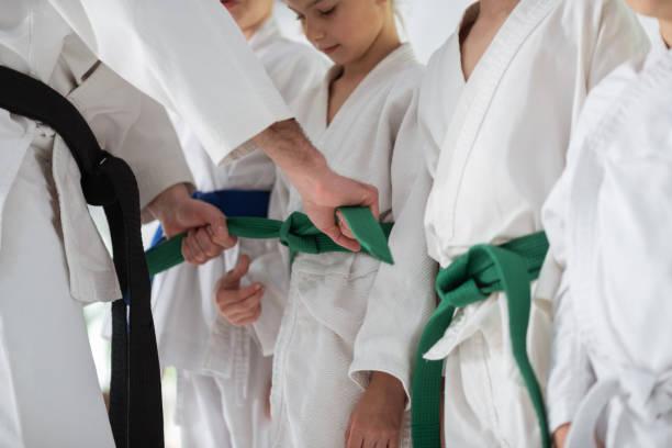Aikido-Trainer bindet Gürtel für seine Schüler vor Wettkampf – Foto