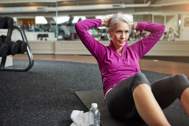 aiming for improved health and wellbeing - sit ups stock photos and pictures