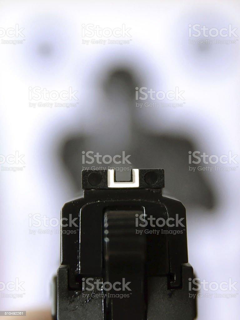 Aiming gun at target stock photo