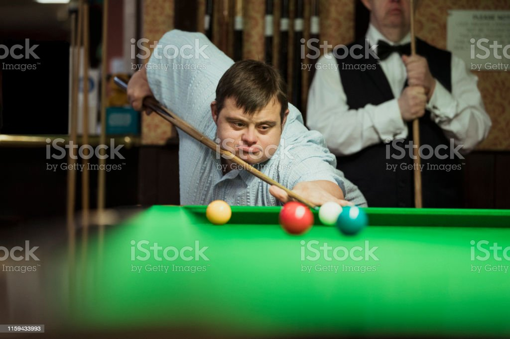 Man with Down syndrome playing snooker, aiming to take a shot.