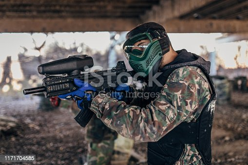One man playing paintball on a rural terrain in abandoned building, man is aiming to shot.