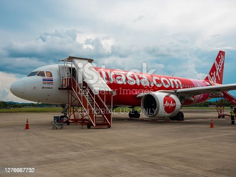 Nan, Thailand - Aug 29th 2020 : Air Asia airplane parking on runway road with stairs prepare for arriving passengers