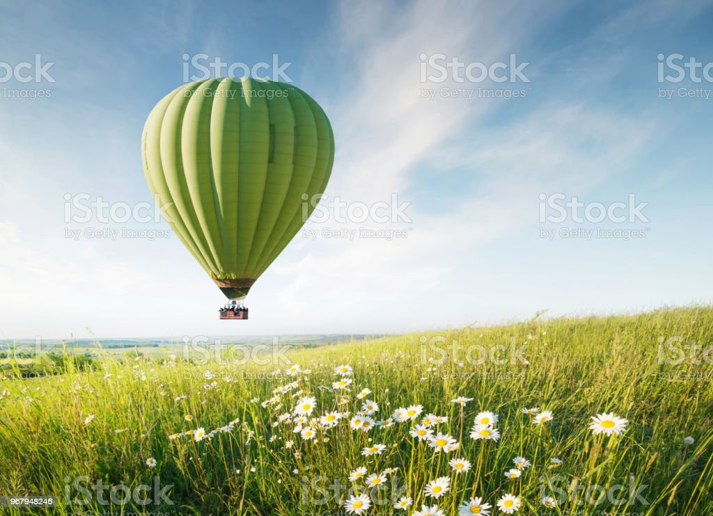 Air ballon above field with flowers at the summer time. Concept and idea of adventure stock photo