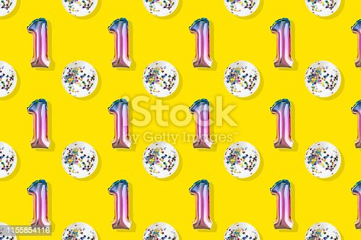 1093222958istockphoto Air Balloons of number one and ball shaped  foil on pastel pink background.  Minimalistic composition of metallic balloon. Holiday celebration.Metallic balloon. 1155854116
