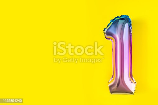 1093222958istockphoto Air Balloons of number one shaped  foil on pastel yellow background.  Minimalistic composition of metallic balloon. Holiday celebration.Metallic balloon. 1155854240
