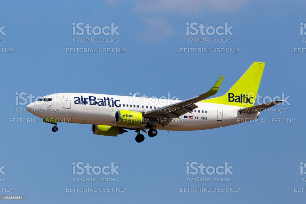 YL-BBJ Air Baltic Boeing 737-300 aircraft on the cloudy sky background royalty-free stock photo