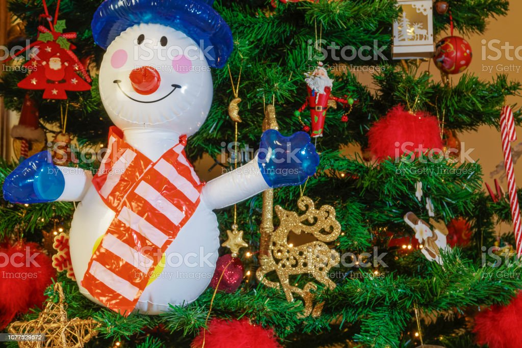 Air blown seasonal figure before an illuminated artificial Christmas tree with lights and colorful decorations. stock photo