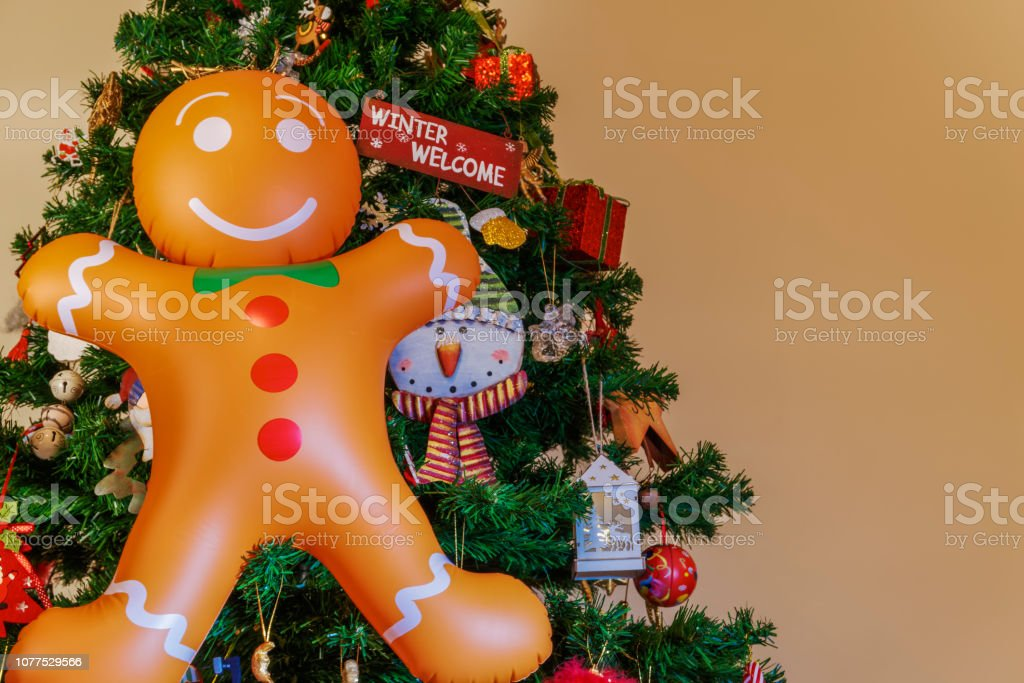 Air blown seasonal figure hanging before an artificial Christmas tree with festive colorful decorations. stock photo