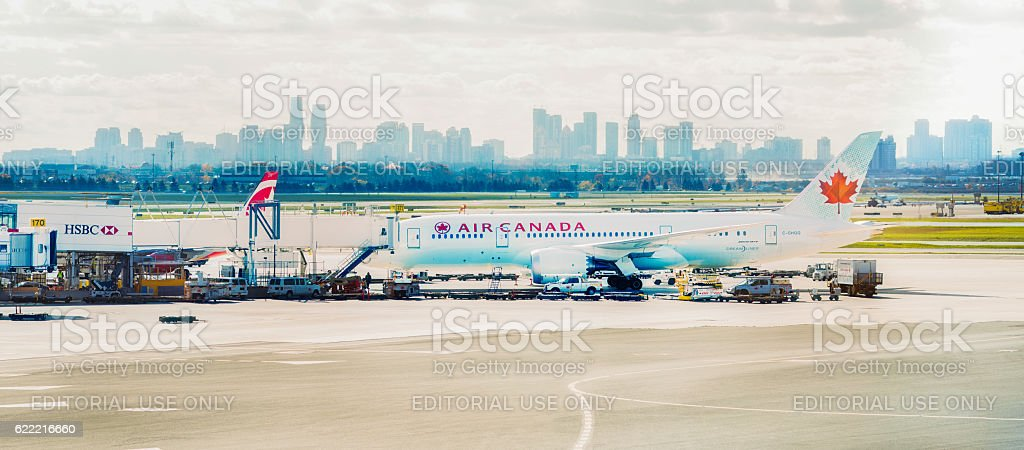 Air Canada Bowing 787 being loaded at airport panorama Toronto, Canada - November 4, 2016: Air Canada Bowing 787 being loaded at airport with Mississauga skyline in the background. Airplane Stock Photo