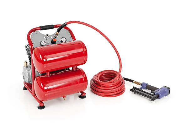 """Air Compressor with a Nail Gun """"Air compressor with a nail gun, isolated on white.Please also see:"""" compressor stock pictures, royalty-free photos & images"""