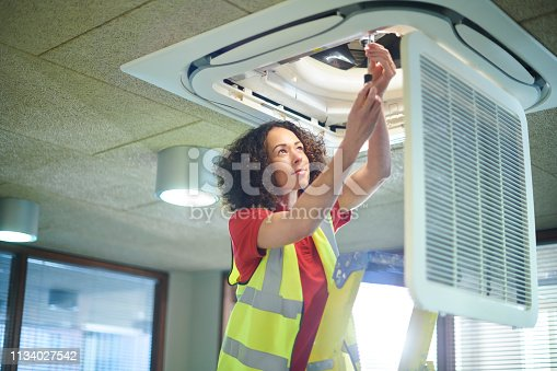 air con maintenance engineer in empty office floor