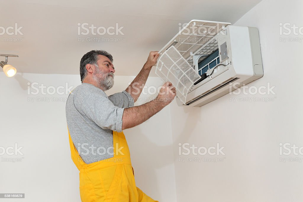 Air condition examine or install Electrician cleaning filter of air condition device in a room 2015 Stock Photo