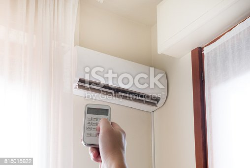 istock Air conditioner and hand with temperature remote control 815015622