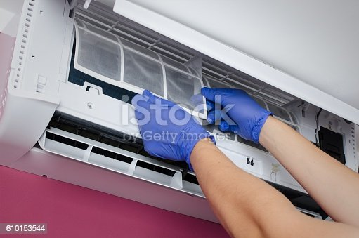 istock Air conditioner cleaning. Man checks the filter. 610153544