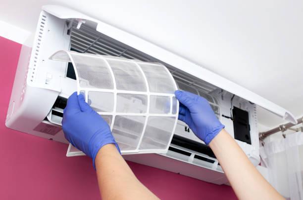 air conditioner cleaning. man checks the filter. - luftfilter stock-fotos und bilder