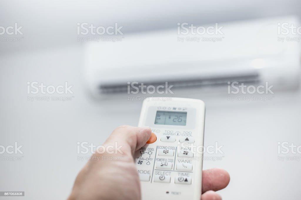 mano de primer plano de aire acondicionado con control remoto - foto de stock