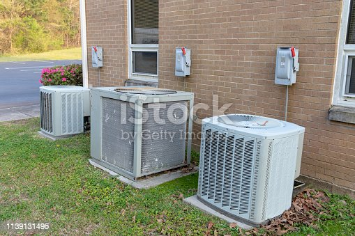 istock Air conditioner compressors outside brick building 1139131495