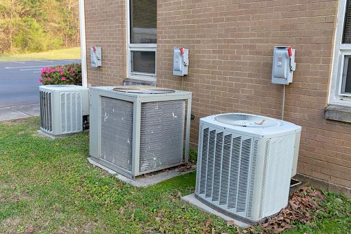 istock Air conditioner compressors outside brick building 1139131495