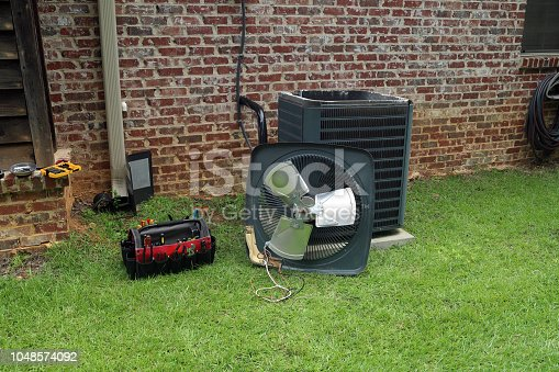 istock Air Conditioner Condenser coil with tools being repaired 1048574092