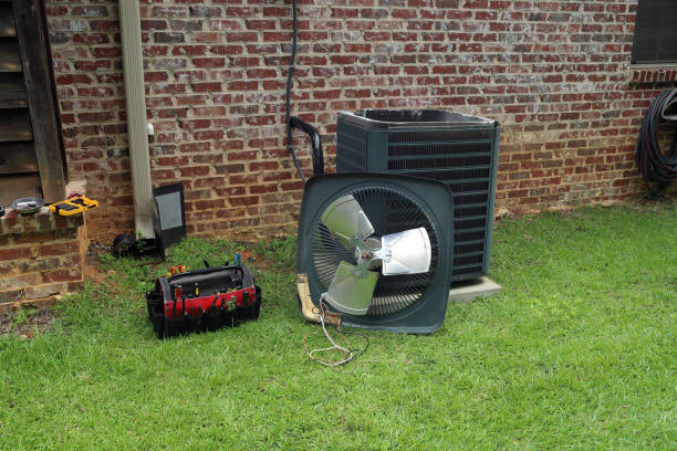Air Conditioner Condenser coil with tools being repaired Air Conditioner compressor condenser coil with fan and tools being worked on next to a brick house for repair maintenance. air duct stock pictures, royalty-free photos & images