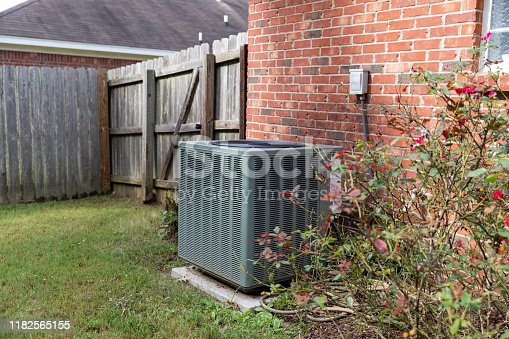 istock Air conditioner condenser unit sitting next to brick home with fence 1182565155