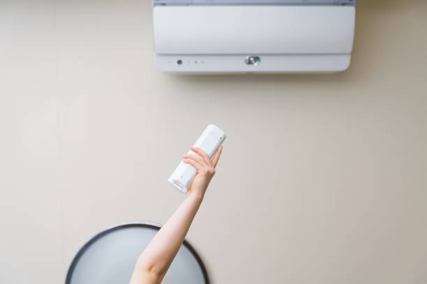 luftkonditionering som styrs av fjärrstyrenhet - kvinna ventilationssystem bildbanksfoton och bilder