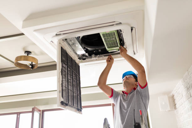 Air conditioner install Electrician fitting air conditioning to office interior household fixture stock pictures, royalty-free photos & images