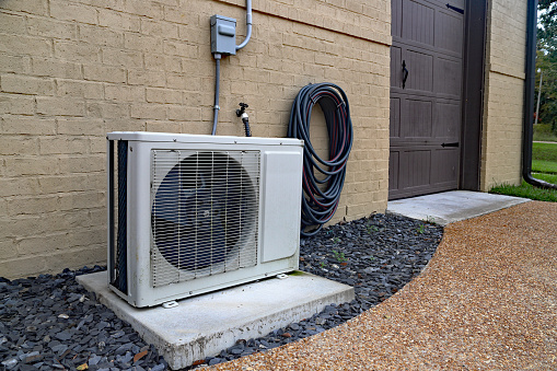 istock Air Conditioner mini split system next to home with brick wall 1064710720