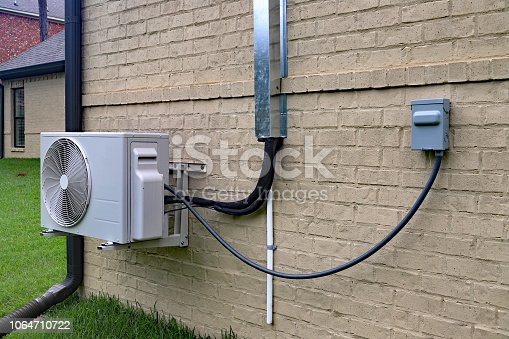 istock Air Conditioner mini split system next to home with brick wall 1064710722