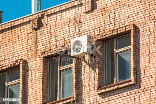 939450782istockphoto Air conditioner on the wall of a brick building between the windows on the top floor 866909808