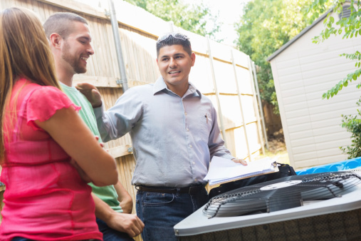istock Air conditioner repairman explaining A/C damage to homeowners 509466683
