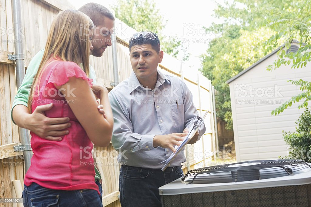 Air Conditioner repairman explaining cost of repairs to homeowners stock photo