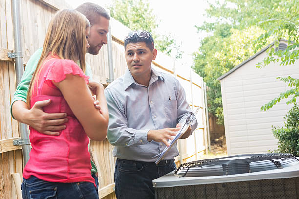 air conditioner repairman explaining cost of repairs to homeowners - repairing stock photos and pictures